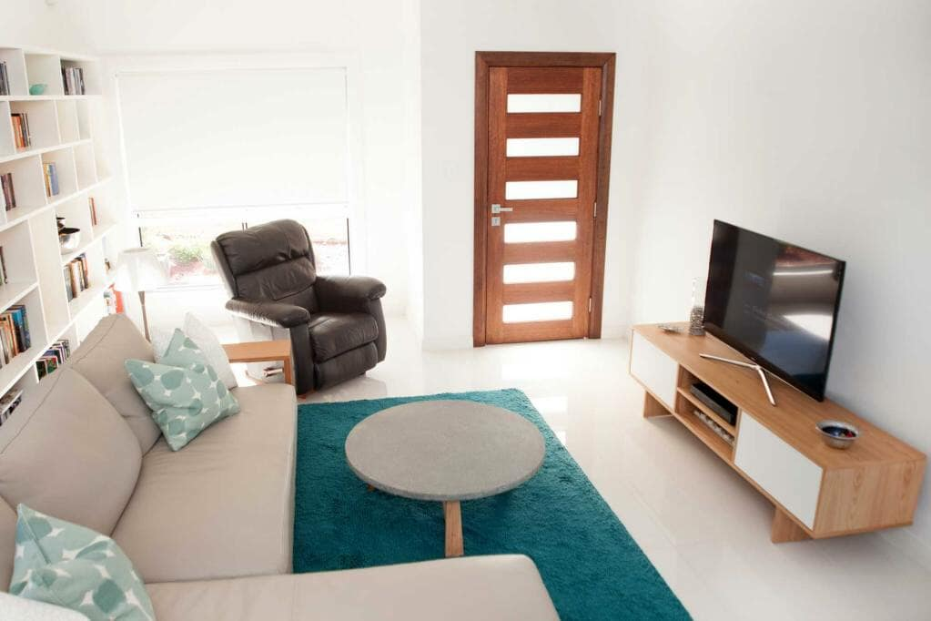 Lounge room with couch and tv by Anoushka Allum Interior Designer